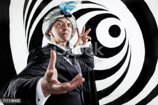 A stock photo of a Hypnotist inducing a trance and gesturing on a black and white swirl background.