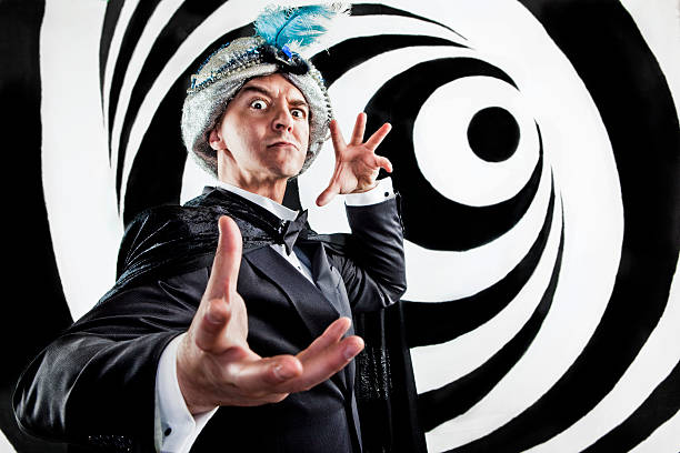 Hypnotist Mind Control A stock photo of a Hypnotist inducing a trance and gesturing on a black and white swirl background. magician stock pictures, royalty-free photos & images