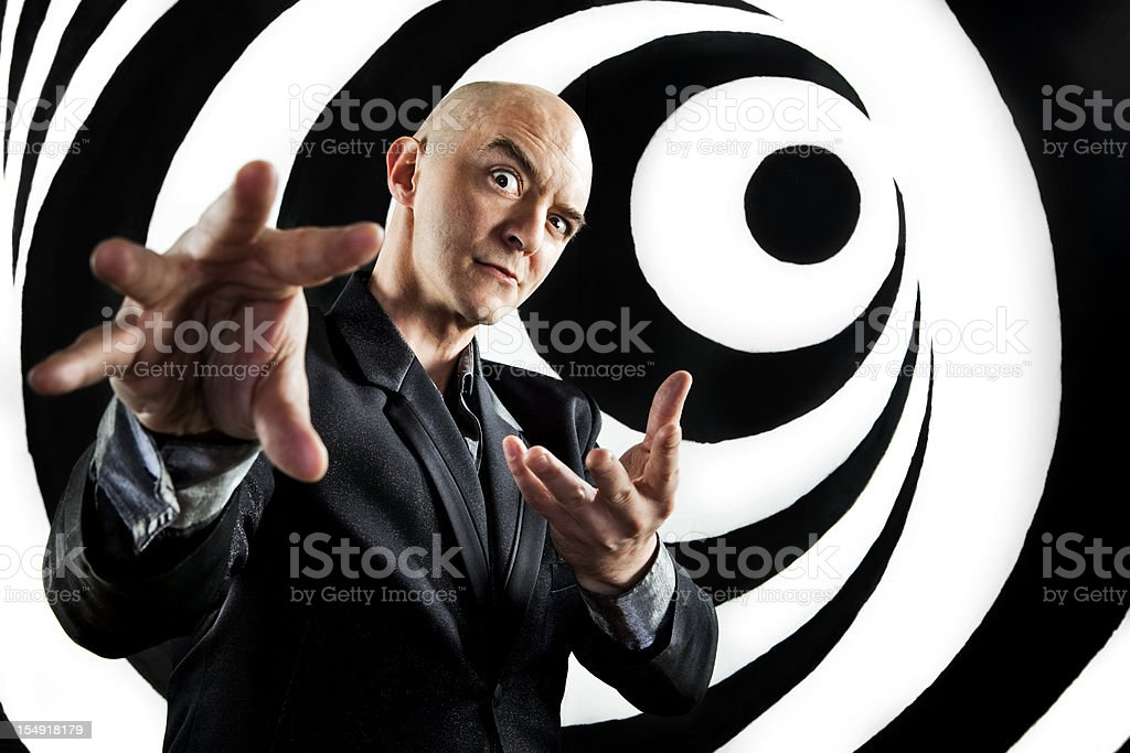 A hypnotist trying to control a person using his hands stock photo