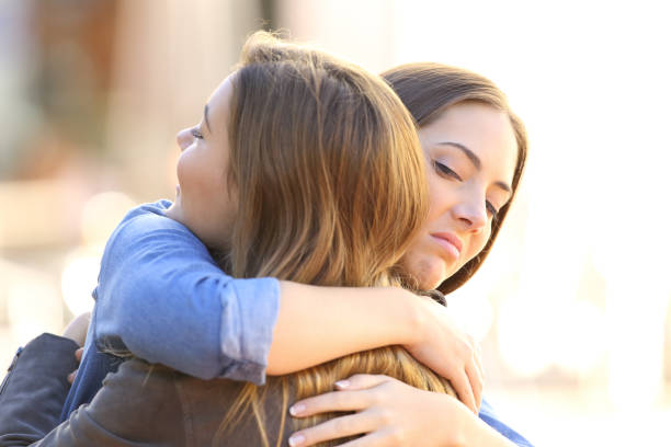 Hypocritical girl embracing a friend stock photo
