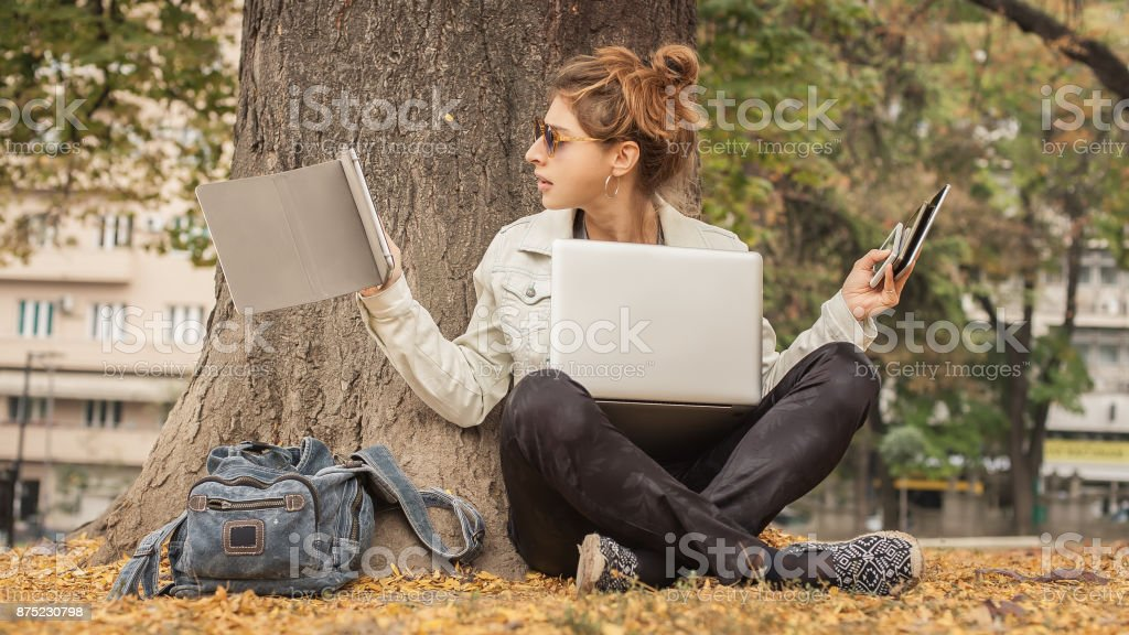 hysterical girl with too many screens mobils tablets and laptops