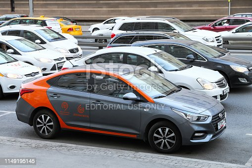 Moscow, Russia - April 19, 2019: Carsharing company Delimobil's Hyundai Solaris in the city street at the background of a traffic jam.