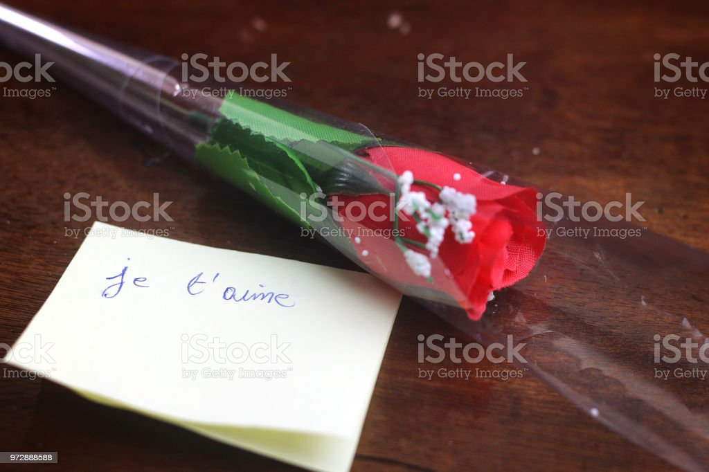 b06b5458e1369 I love you translated in french written on yellow card with red flower -  Stock image .