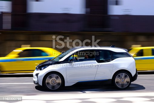 BMW i3 five-door urban electric car driving in the city of Funchal at Madeira island, Portugal. BMW i3, previously Mega City Vehicle (MCV) and is BMW's first zero emissions mass-produced vehicle due to its electric powertrain.