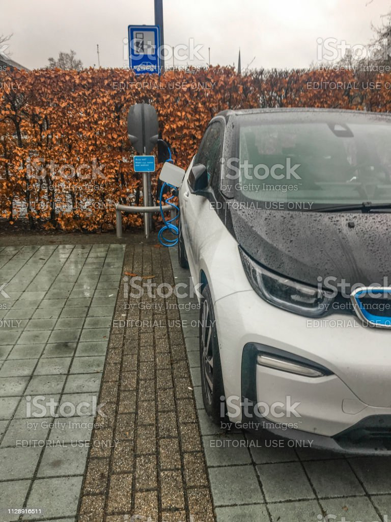 BMW i3 five-door urban electric car next to a charging station stock photo