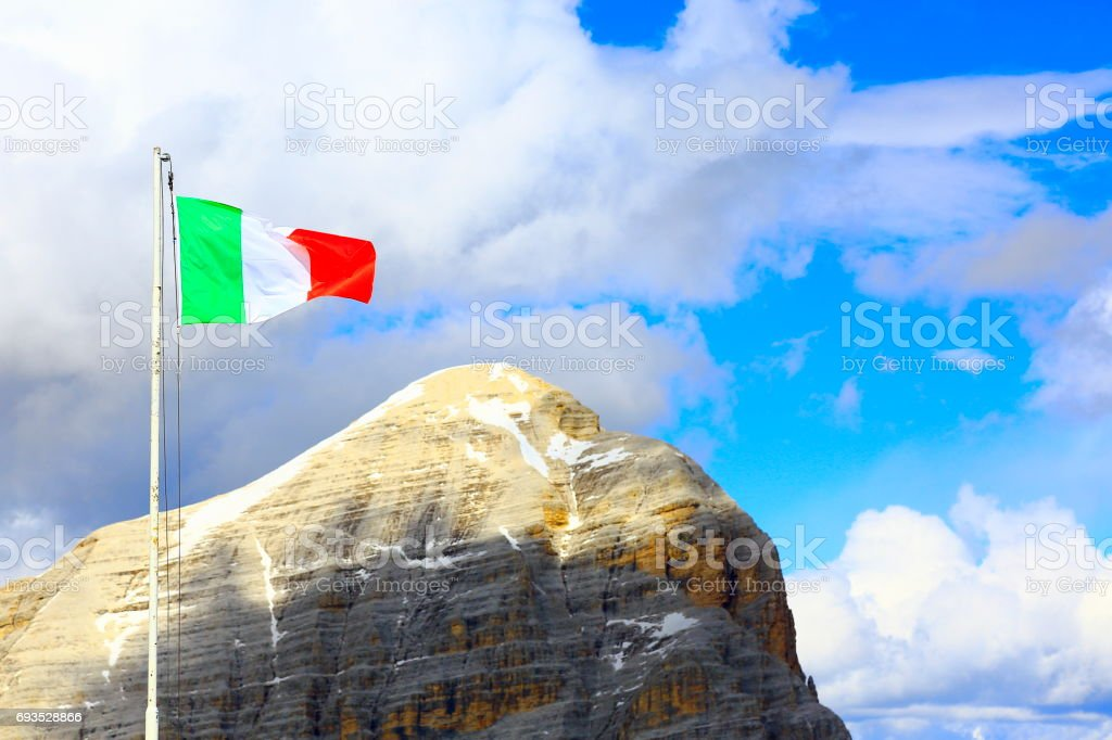 Ialian flag winding above Tofano - Idyllic Lagazuoi summit panorama, Cinque Torri Dolomites, pinnacles mountain range, dramatic and majestic Italy tirol alps stock photo