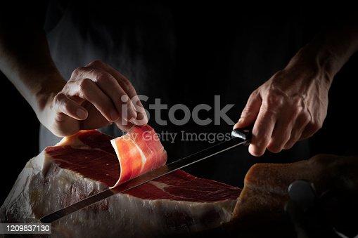 Iberian ham serrano ham slice cutting hands and knife hands on dark background low key