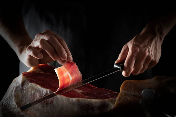 Iberian ham serrano ham slice cutting hands and knife Iberian ham serrano ham slice cutting hands and knife hands on dark background low key iberian stock pictures, royalty-free photos & images
