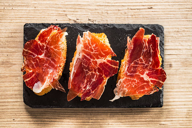 Jamon iberico tapas Jamon iberico, the best spanish ham tapas. Top view on a wooden table. iberian stock pictures, royalty-free photos & images
