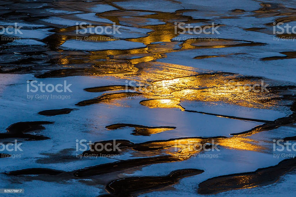 Ice And Fire Warm light of winter sunset reflects in the ice of the frozen river. The contrast of warm and cold colors. Ice And Fire Agricultural Field Stock Photo
