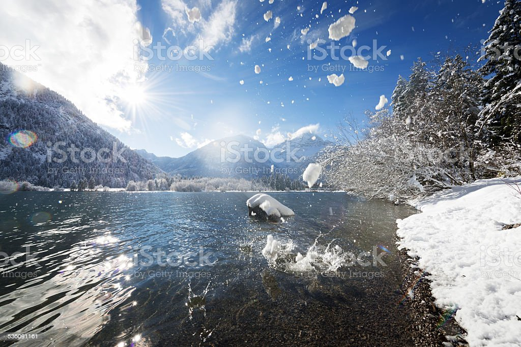 ice and snow pieces flying into lake stock photo