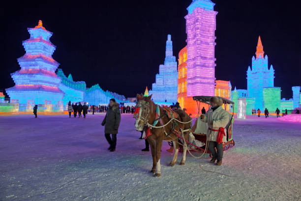 Ice and Snow World, Harbin, China December 27, 2018, A horse pulled colorful illuminated carriage in ice and snow world, Harbin, Heilongjiang Province, China harbin stock pictures, royalty-free photos & images