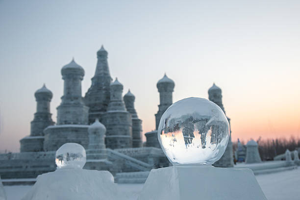 Ice ball in front of russian style ice p Harbin, China - January 21, 2016:  Ice ball in front of russian style ice palace at sunset harbin stock pictures, royalty-free photos & images
