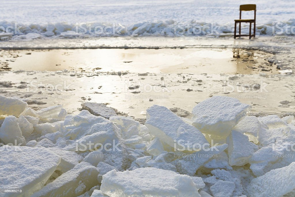 ice blocks and chair on edge of ice-hole stock photo