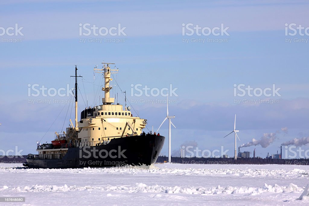ice breaker ploughing the icefield, wind turbines in arctic environment royalty-free stock photo