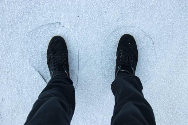 Ice breaking under mans legs stock photo