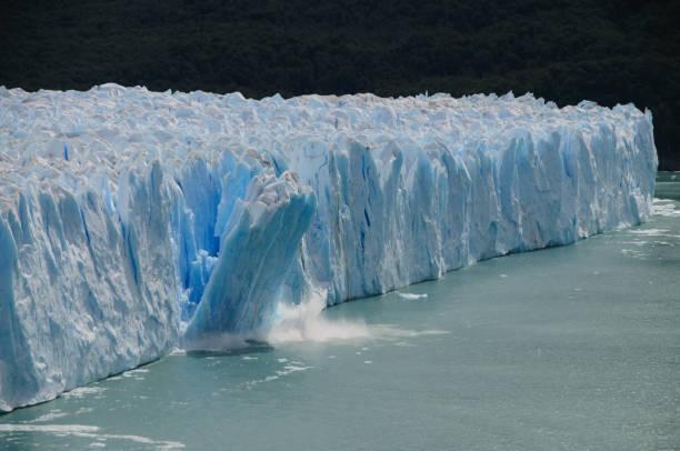 ice calving at the perito moreno glacier - iceberg stock photos and pictures