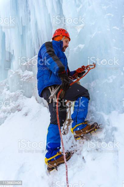 Photo of ice climber checks the reliability of the anchor