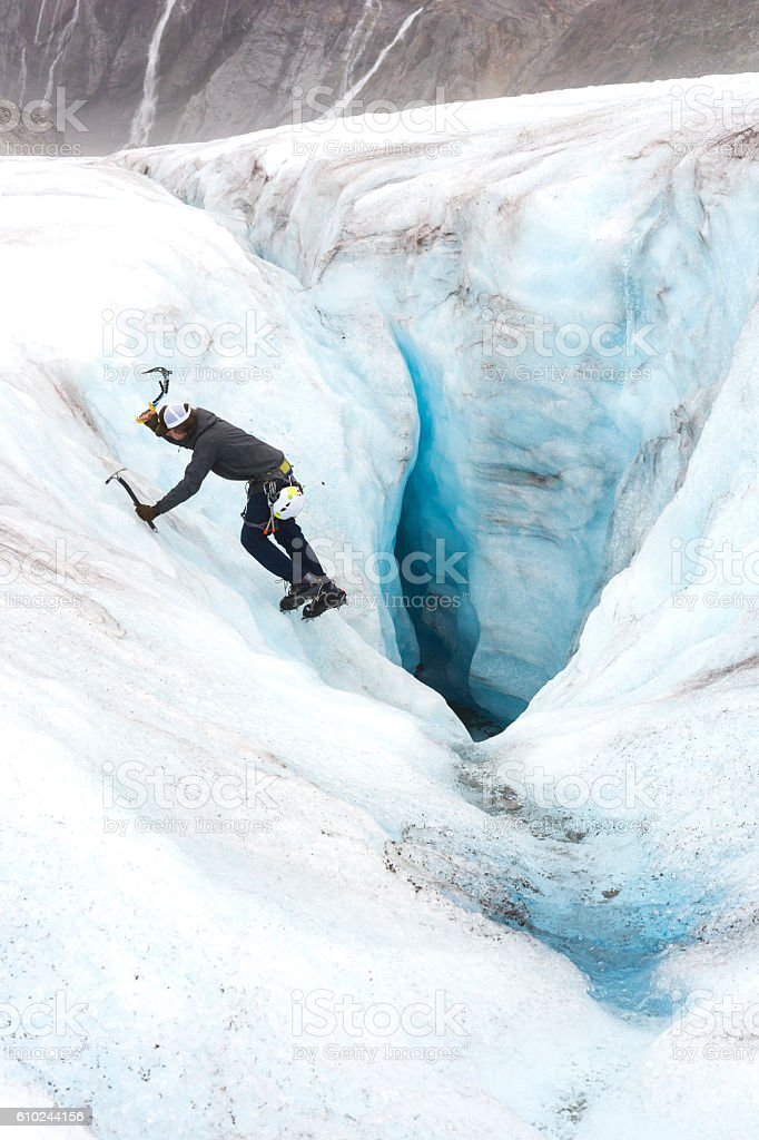 Ice climber descending a crevasse stock photo