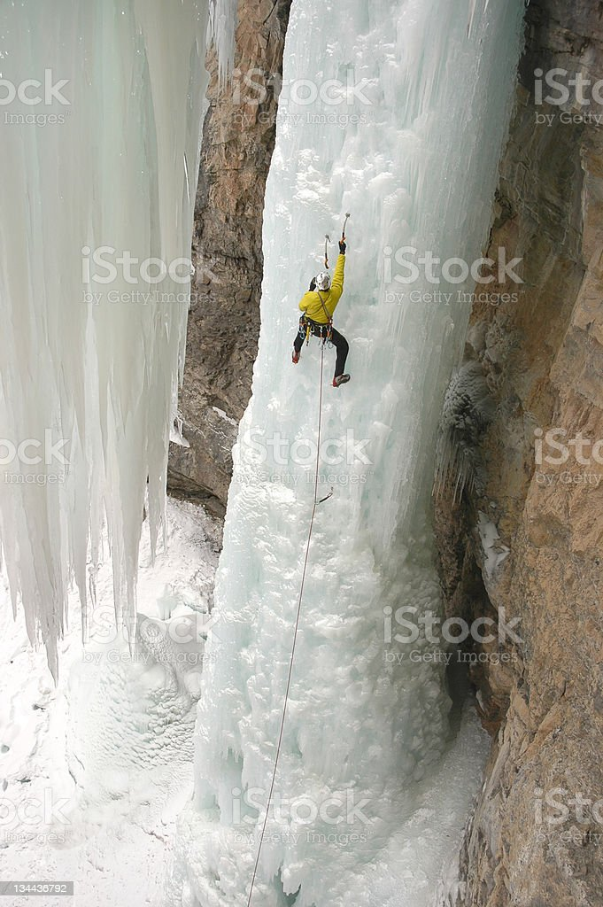Ice Climber Extreme Adventurer on Steep Frozen Waterfall royalty-free stock photo