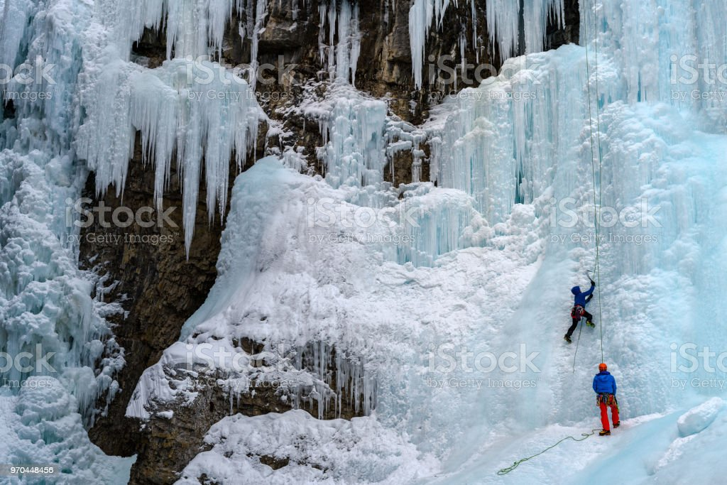 Ice climber on the frozen Upper Falls of the Johnston Creek during winter stock photo