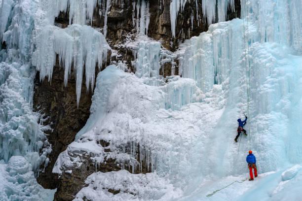 冬の間にジョンストン クリークの冷凍の上滝のアイスクライマー - アイスクライミング ストックフォトと画像