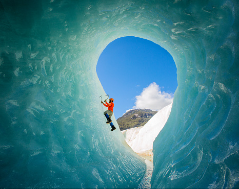 A solo male ice climber working his way up on an ice wall in a glacier. Lifestyle image created from the inside of an ice cave.