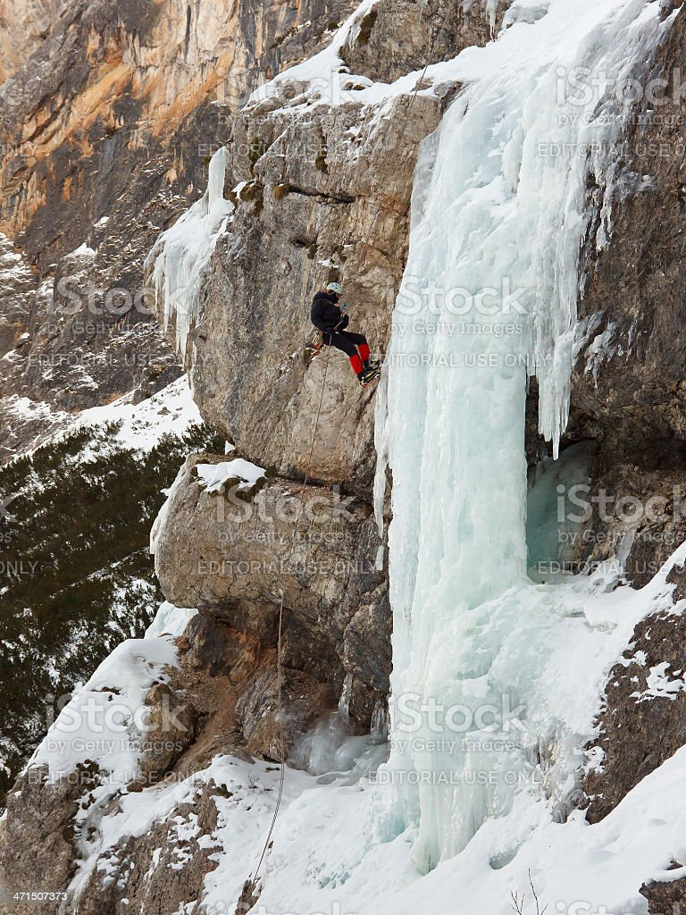 Ice Climber Rappelling Down Frozen Waterfall stock photo
