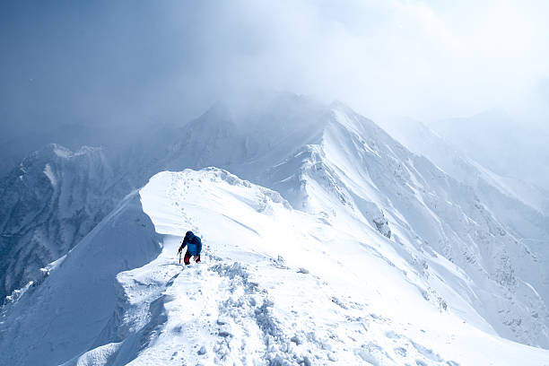 ice climber walks along mountain peak - snowy mountains stock photos and pictures