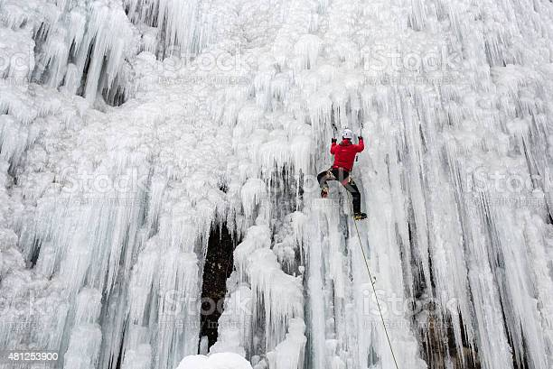 An adventurous  fixing the ice axe on ice-covered rock face during ice climbing.