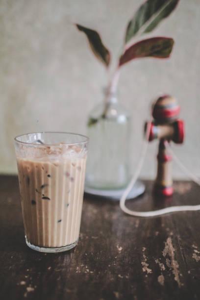 eiskaffee und milch auf rustikalem holztisch ablegen, schwarzen eiskaffee mit milch oben schließen, selektiver fokus, freier raum für text und getöntes bild - hausgemachter eiskaffee stock-fotos und bilder