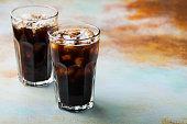 背の高いグラスに注がれるクリームとコーヒー豆のアイス コーヒー。コピー スペースとさびた青地に冷たい夏の飲み物