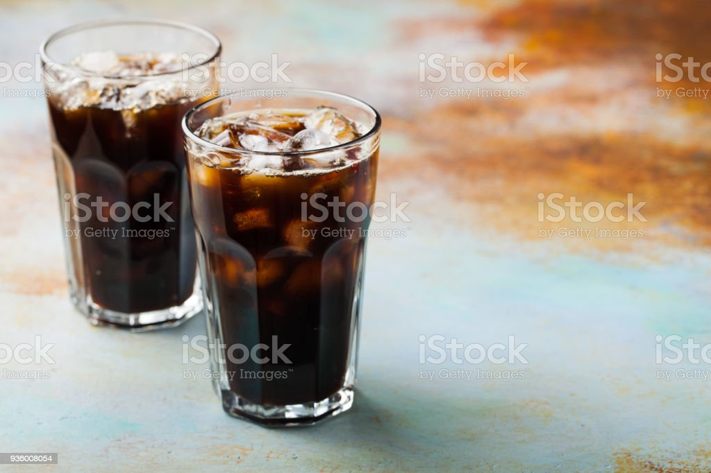 Ice coffee in a tall glass with cream poured over and coffee beans. Cold summer drink on a blue rusty background with copy space stock photo