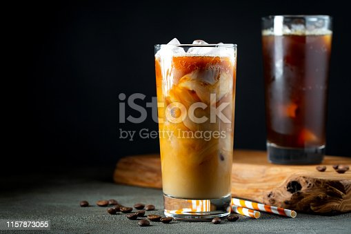 Ice coffee in a tall glass with cream poured over, ice cubes and beans on a old rustic wooden table. Cold summer drink with tubes on a black background with copy space.