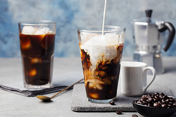 Ice coffee in a tall glass with cream poured over Ice coffee in a tall glass with cream poured over and coffee beans on a grey stone background vietnamese culture stock pictures, royalty-free photos & images