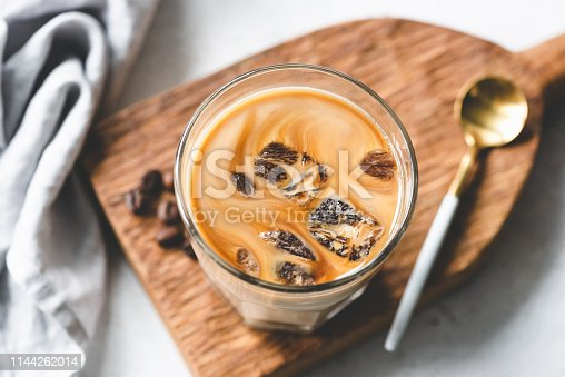 Ice coffee in glass on wooden board, closeup view