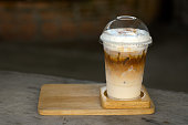 Ice coffee with creamy milk in a plastic glass is on a saucer wood, selective focus, latte art