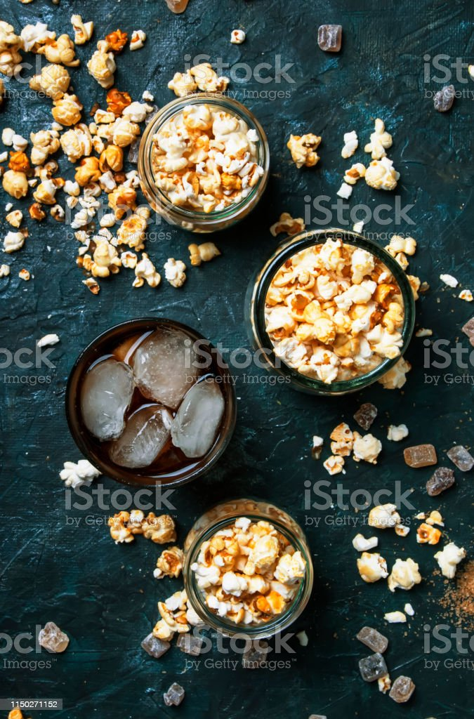 Ice cola and caramel popcorn, unhealthy food and drink, black table,...