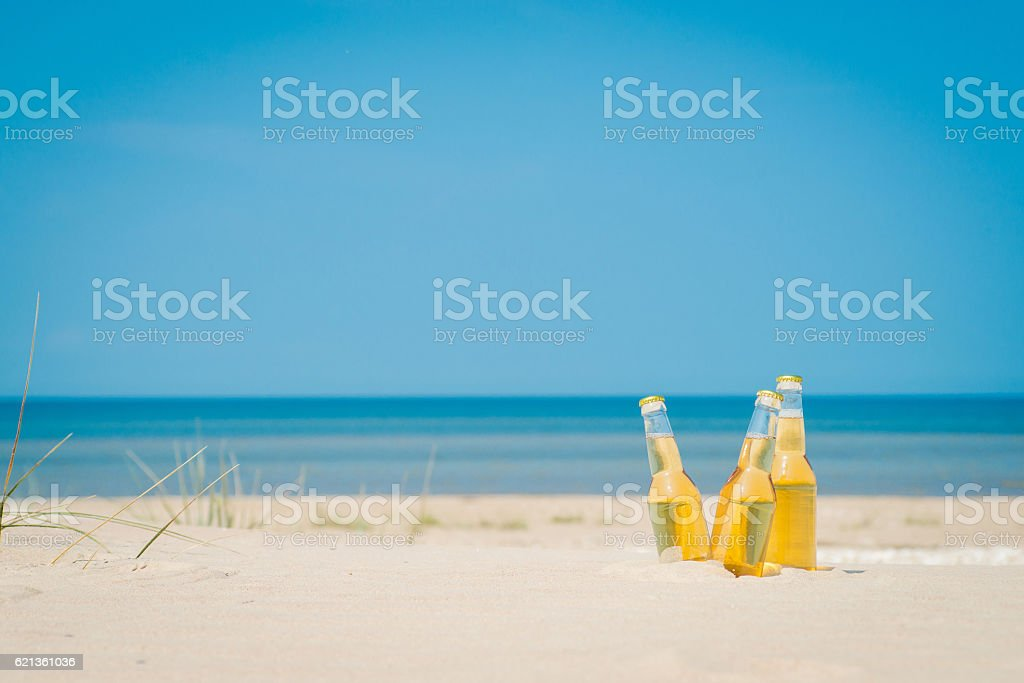 Ice cold beer bottles in the sand under the sun stock photo