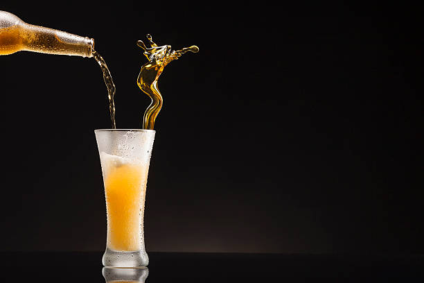 ice cold beer pour from bottle to glass  with condensation - beer pour stock photos and pictures
