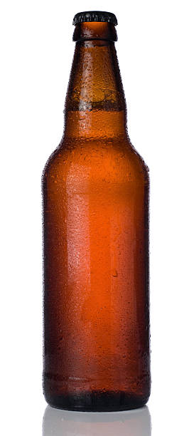 ice cold bottle of beer isolated on a white background - dark beer stock photos and pictures