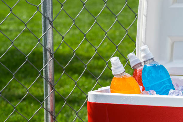 Ice cold colorful sports drinks on ice in cooler on a hot day stock photo