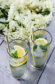 Cold Elderberry flower refreshment with lemon, ice cubes and mint served on white rustic table with wicker basket full of elderberry flowers in background.