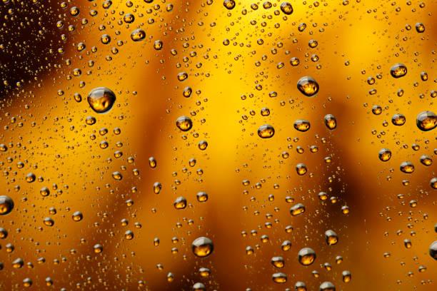 Eis, kaltes Glas mit Wasser bedeckt, Tropfen Kondenswasser Kaltgetränk Wassertropfen goldgelb - orange trinken Hintergrund Regentropfen Textur hautnah – Foto