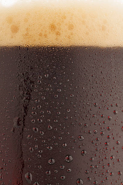ice cold  glass of dark beer  covered with water drops - dark beer stock photos and pictures