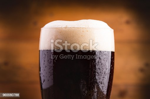 Ice cold glass of dark beer covered with water drops
