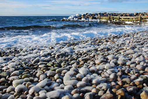 Ice covered pebbles by the coast