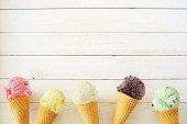 istock Ice cream cone bottom border with a variety of flavors, top down view over a white wood background 1245283563