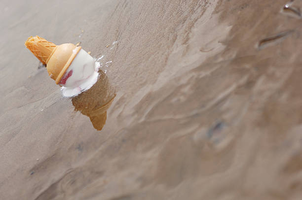 ice cream cone dropped on the beach, accident - ice cream cone stock photos and pictures