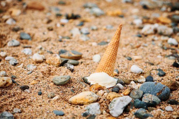 ice cream cone dropped on the beach. - ice cream cone stock pictures, royalty-free photos & images